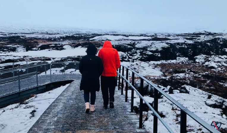 Couple wrapped up warm and out for a walk in the snow